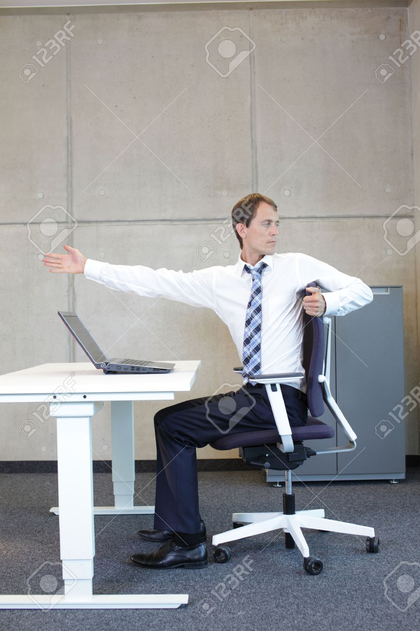 stock photo exercises in office business man taking short break for stretching in sitting position at the desk - Office Chair For Short Person
