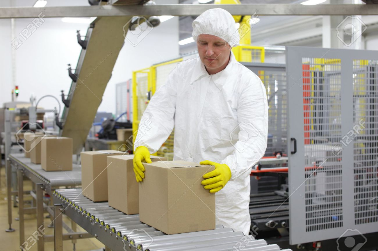 Manual worker in white uniform,cap and yellow gloves, at production line dealing with boxes - 35709835