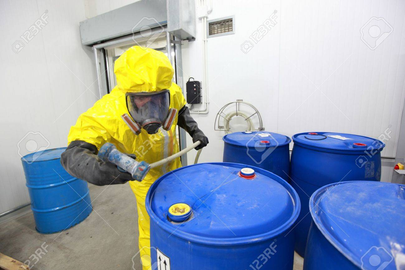 Professional in uniform preparing to fill barrels with chemicals - 35709962