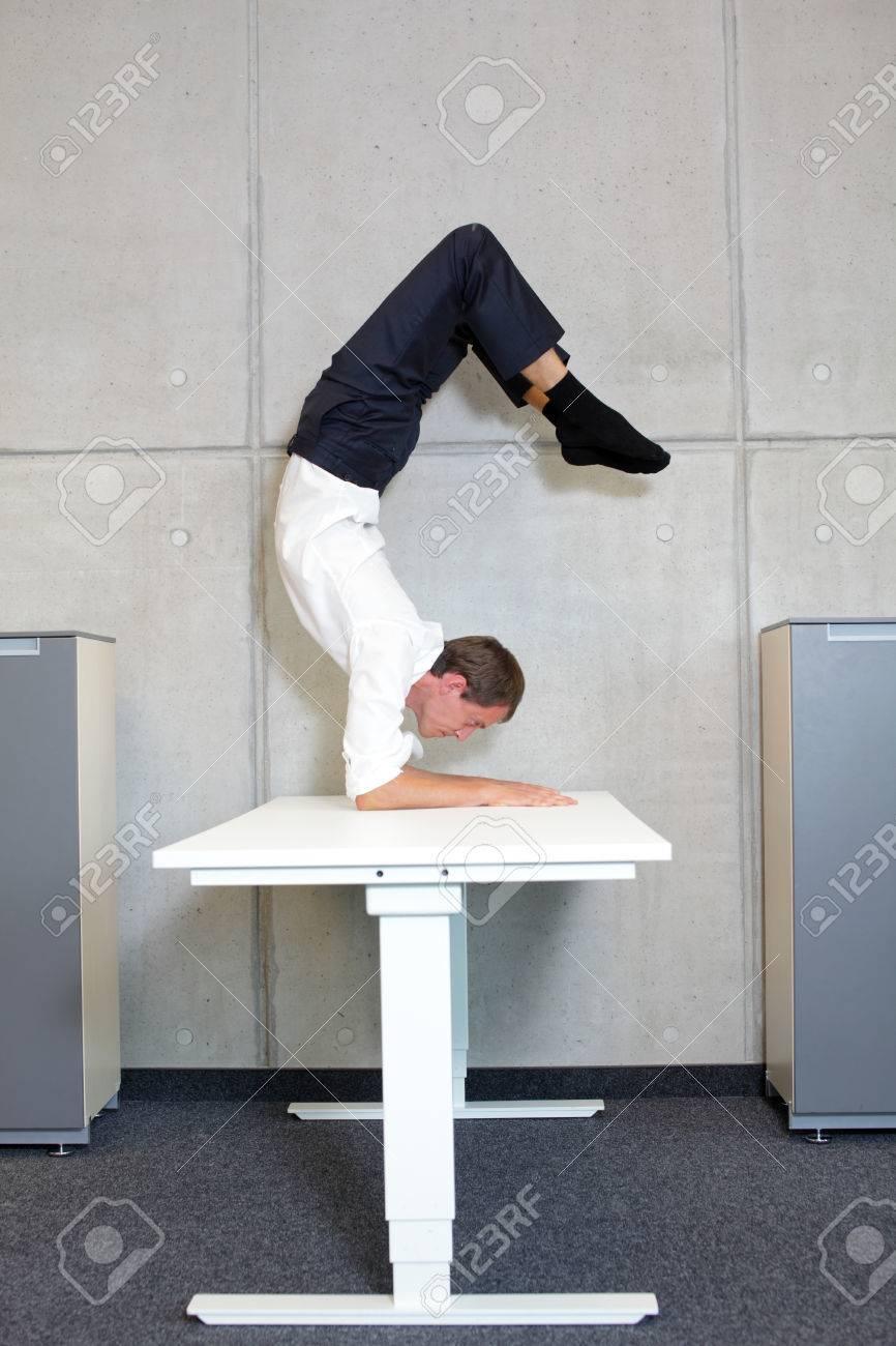 Fit, Flexible Business-Mann Im Skorpion Asana Auf Schreibtisch In ...