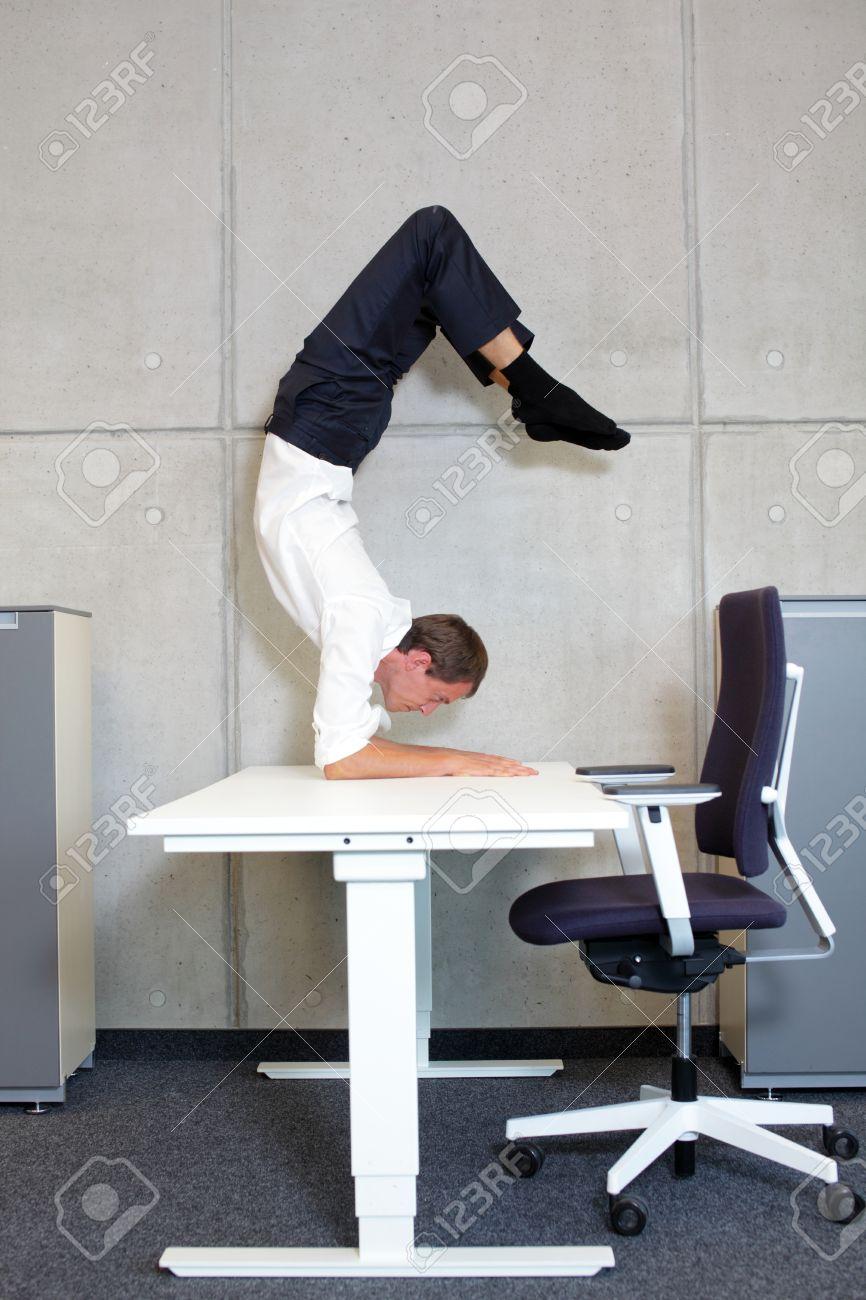 fit,flexible business man in scorpion asana on desk in his office - 38259009