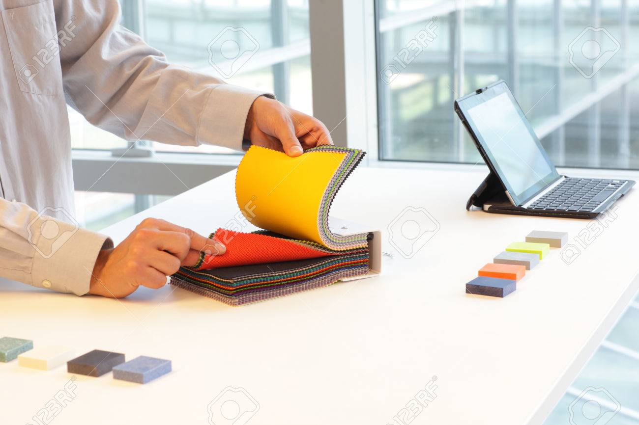 Designer Browsing Coloful Textiles In Sample Book   Interior Design Office  Stock Photo   43622829
