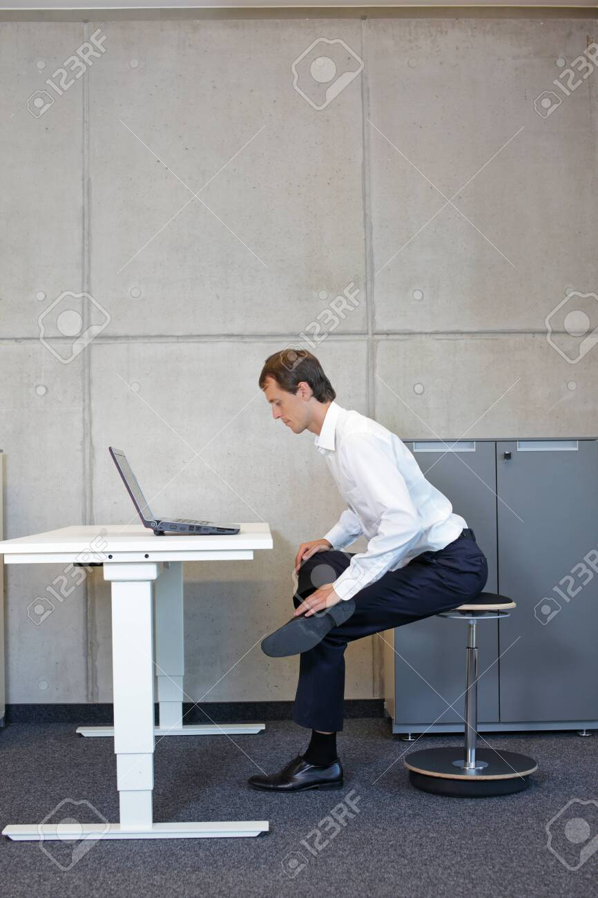 Business man exercising on pneumatic leaning seat with laptop at electric height adjustable desk in office - stretching at desk - 135647912