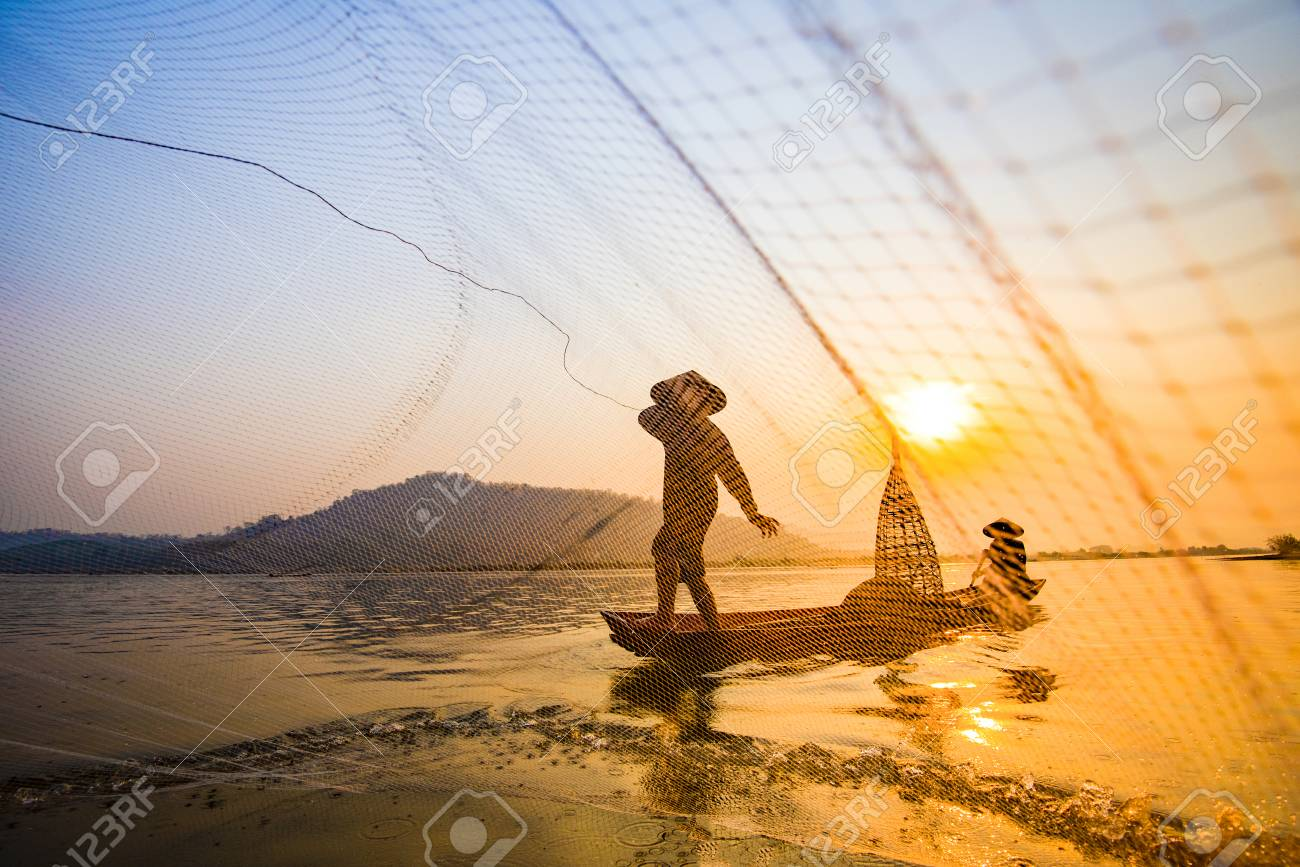 Fisherman on boat river sunset / Asia fisherman net using on wooden boat casting net sunset or sunrise in the Mekong river - Silhouette fisherman boat with mountain background life person countryside - 115051981