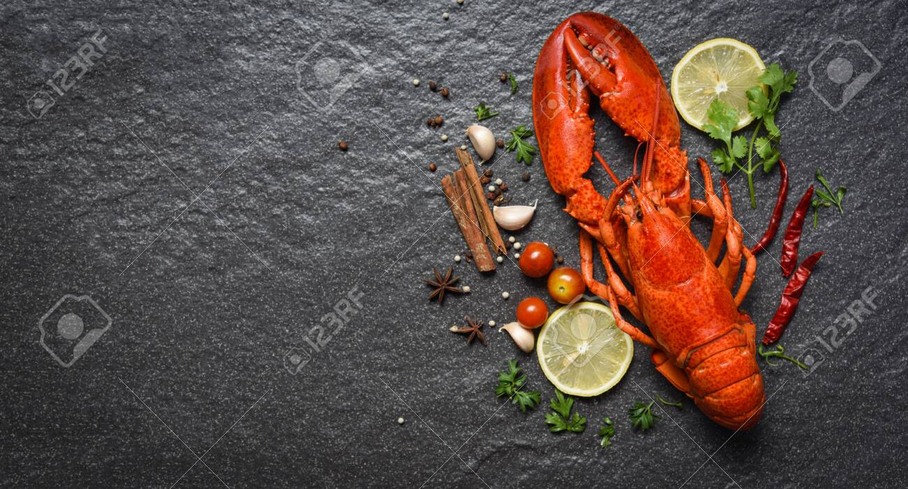 Red lobster seafood with lemon herbs and spices on dark backgroud top view copy space - 120493604
