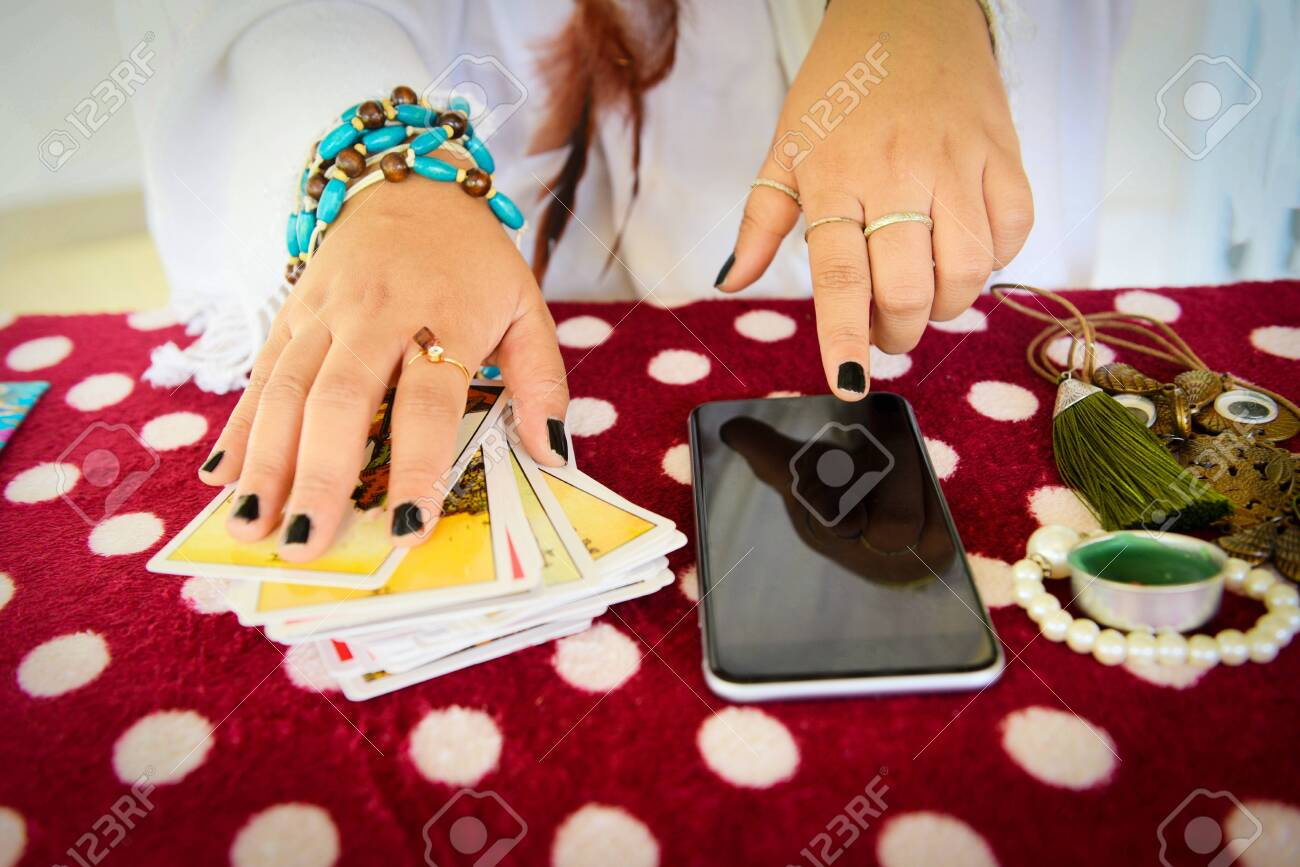 Fortune teller reading fortune lines on screen smartphone modern horoscopes online fortune telling application Palmistry Psychic readings and clairvoyance hands concept with Tarot cards divination - 128029274