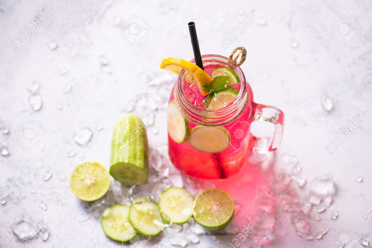 Exotic summer drinks refreshing of cold drinks glasses jar fresh fruit and vegetable on ice homemade cocktail tea with mojito lemon lime and cucumber, Colorful summer drink juicy red pink - 173374716