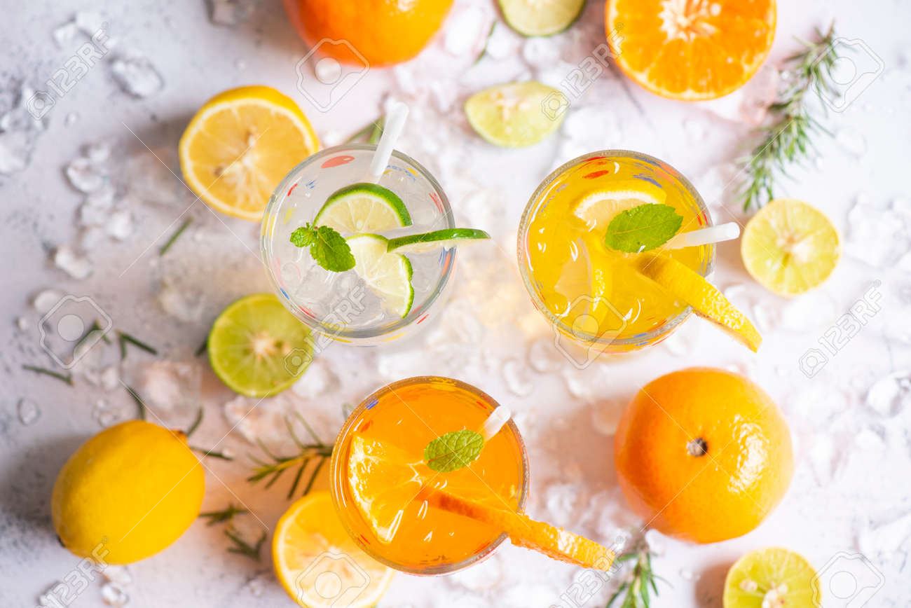 Colorful summer drink juicy, Exotic summer drinks refreshing variety of cold drinks glasses fresh fruit on ice homemade cocktail tea with mojito lemon lime orange rosemary and mint leaf - 173374799