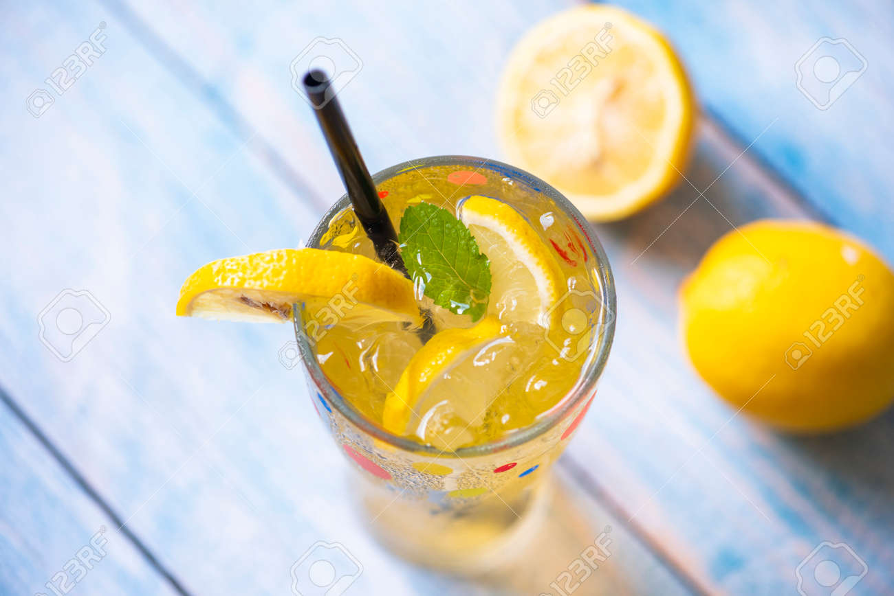 Exotic summer drinks refreshing of cold drinks glasses fresh fruit on ice homemade cocktail tea with lemon and mint leaf, Colorful summer drink juicy lemon slice - 173374778