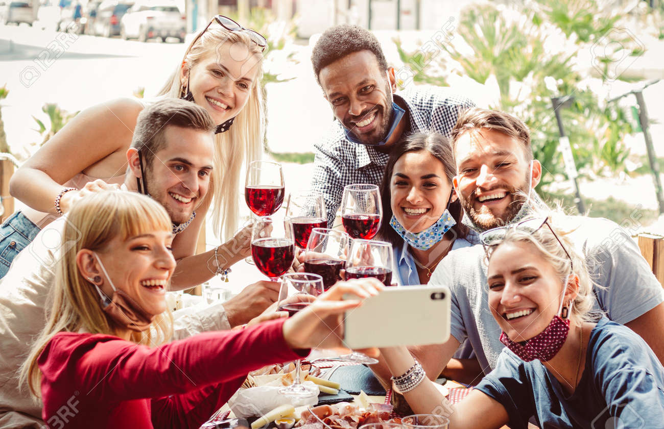Multiracial group of friends wearing protection mask at the restaurant. Happy people celebrating toasting red wine taking a selfie with smartphone. - 159883930