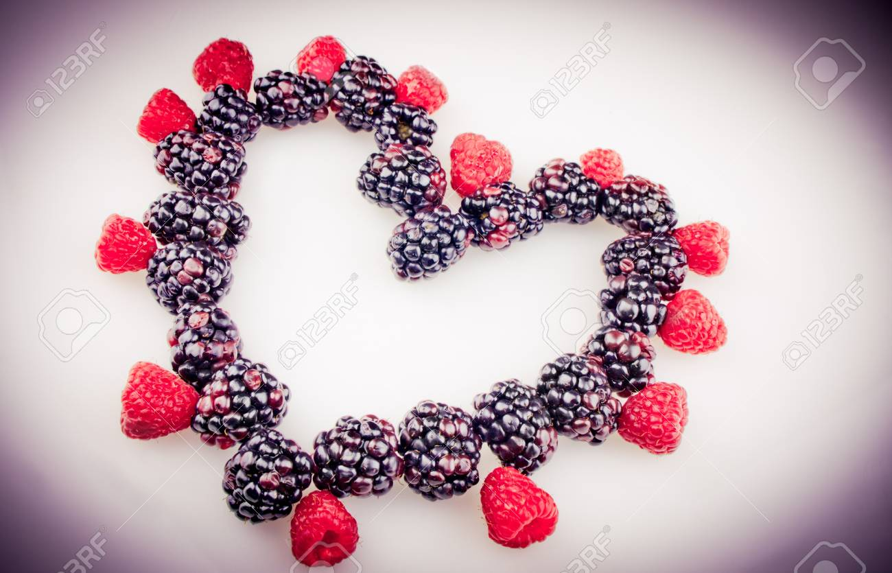 A heart shape of raspberries and blueberries with a purple vignette Stock Photo - 14661737
