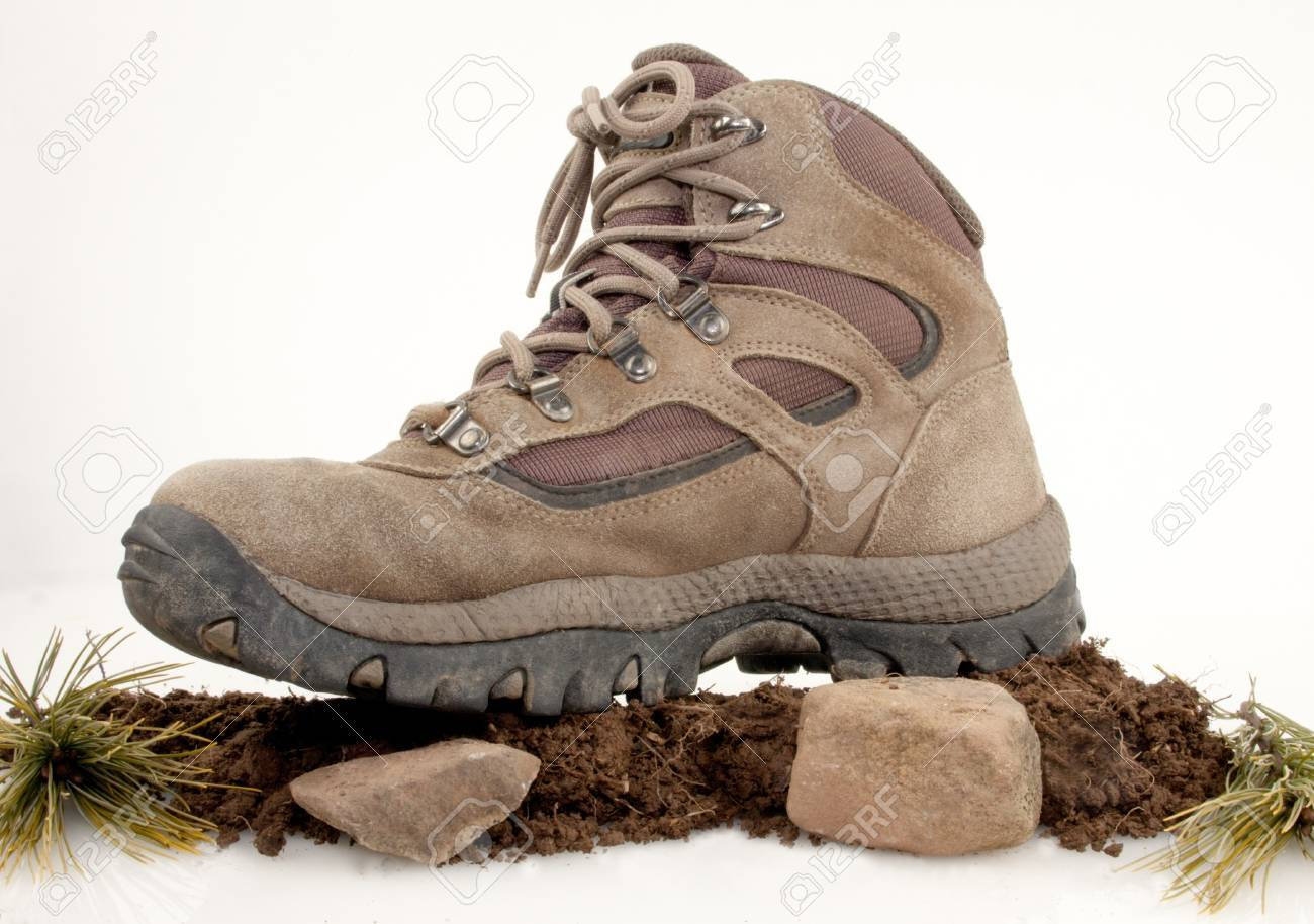 Hiking boot on top of dirt, rocks and green leaves isolated on white Stock Photo - 17089770