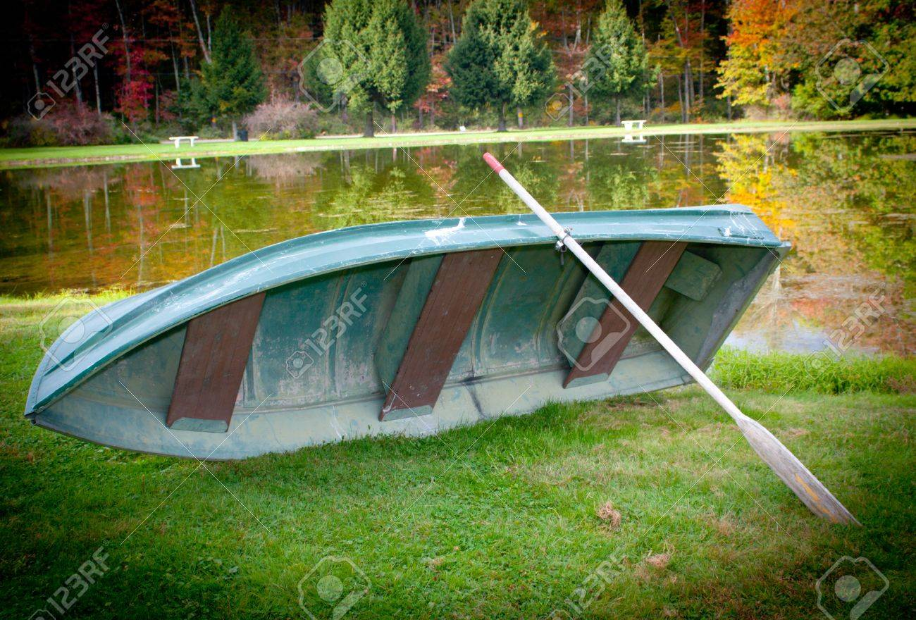 A Boat With A Paddle On A Lake In The Fall Season With Trees.. Stock ...