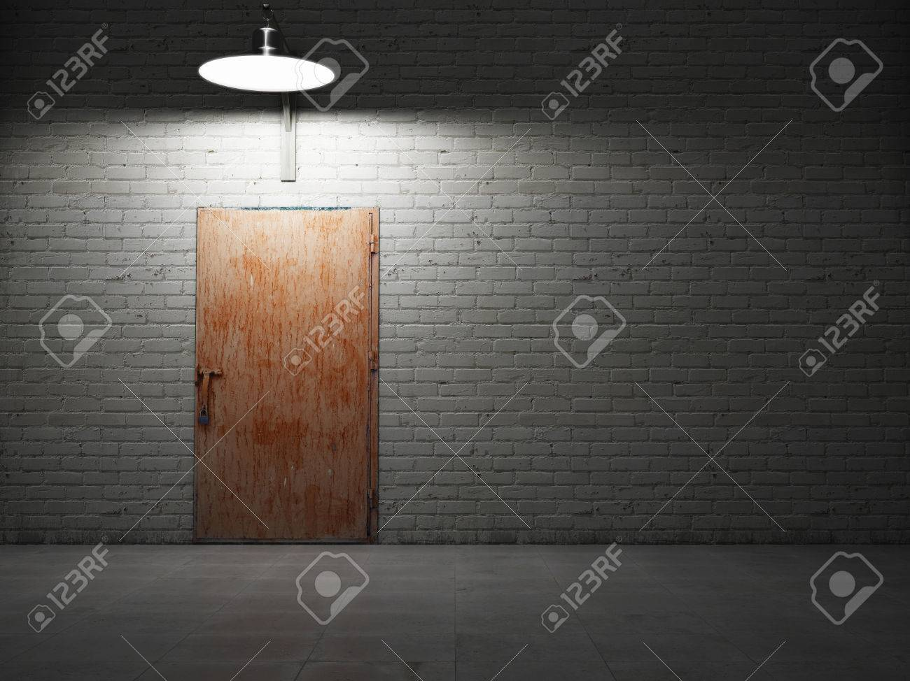 Dirty brick wall illuminated by lamp with rusty metal door Stock Photo - 23182051