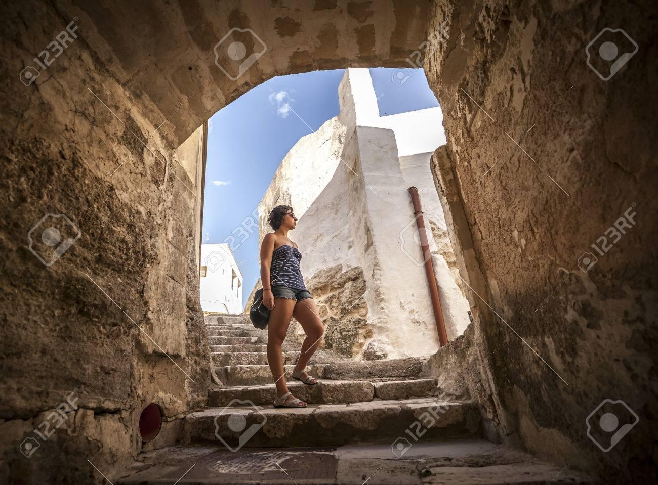 女の子は、ジノーザ、マテーラのよう南イタリアの村の通りの典型的な ...
