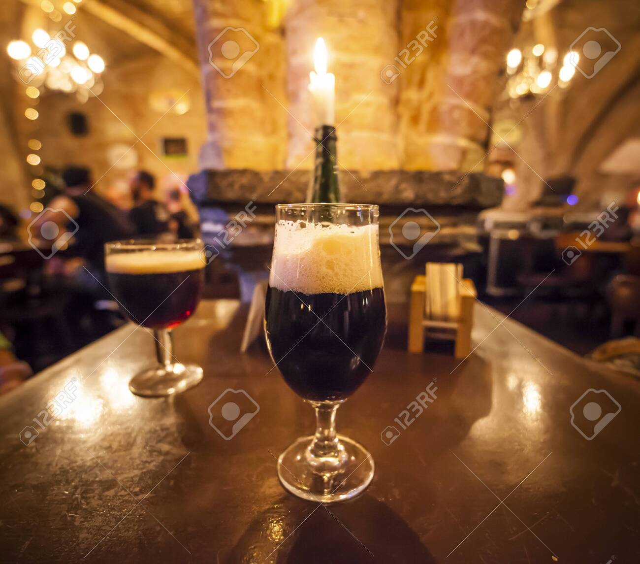 Two glasses of craft beer and a romantic candle in a typical belgian pub - 136076221