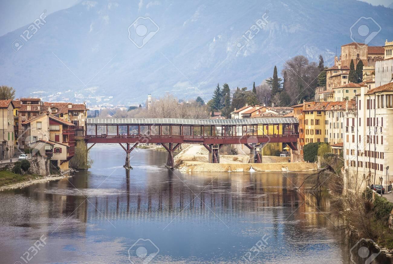 Bridge Ponte degli Alpini at river Brenta in Bassano del Grappa, Italy. Panoramic view at old town with vintage building and wooden bridge - 147193802