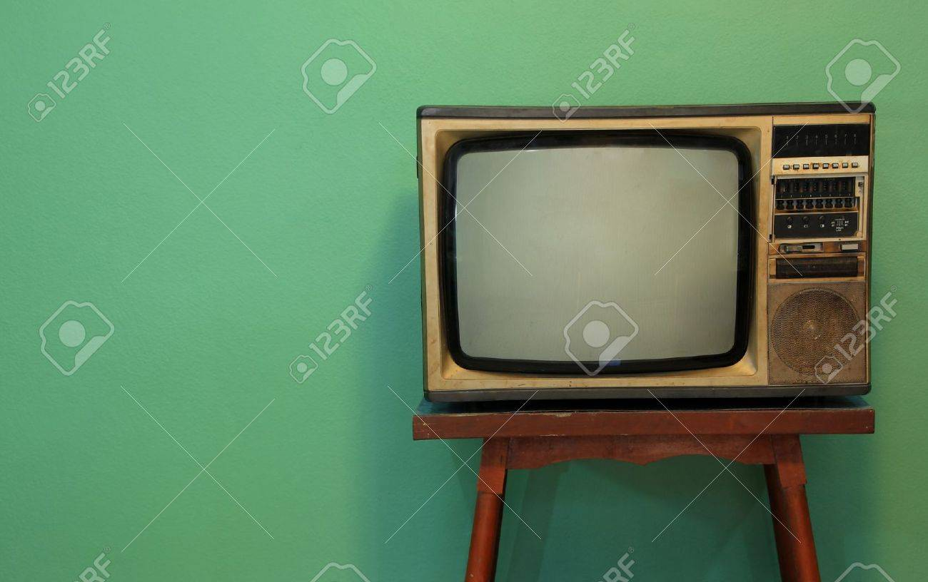 A Retro TV On Old Wooden Table With Green Paint Wall Background ...