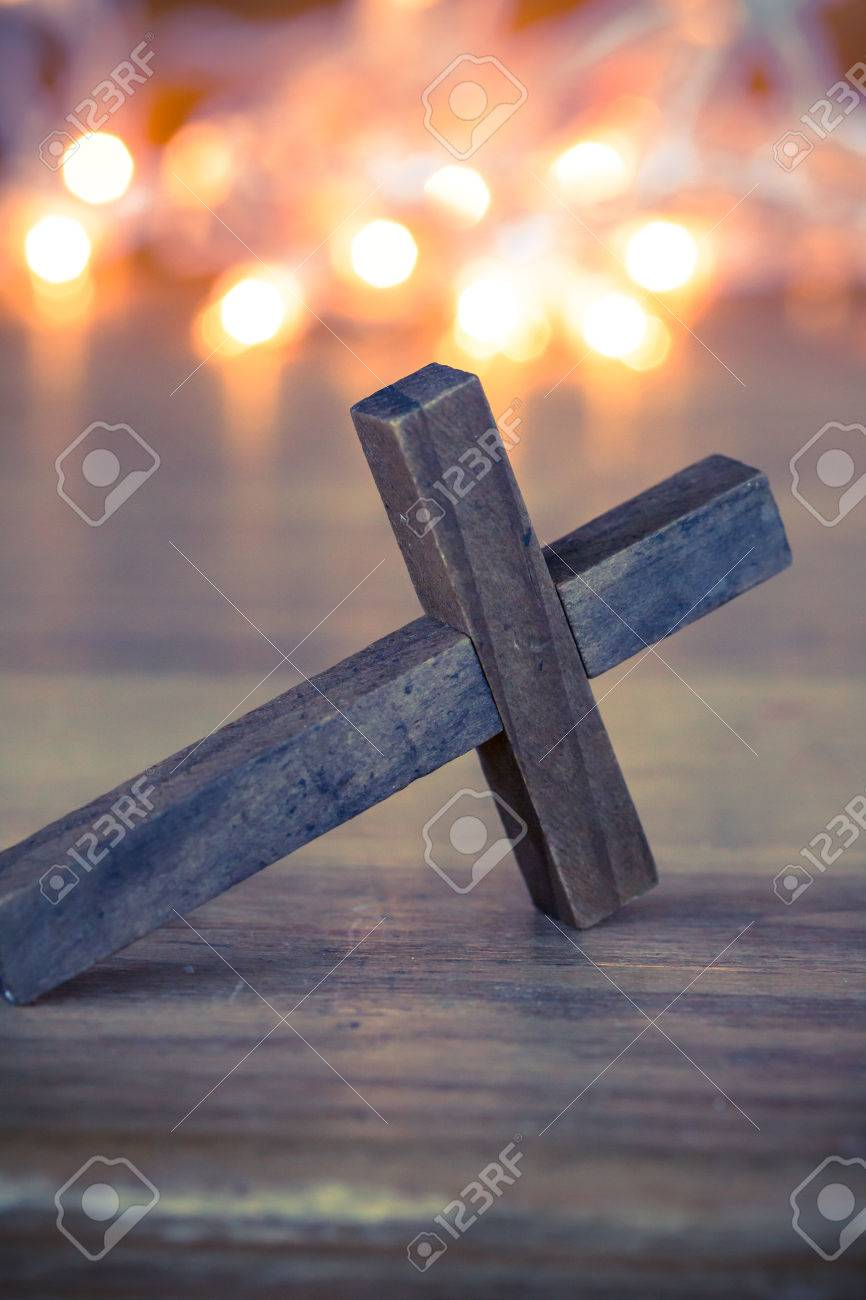 A wooden Christian cross with a soft bokeh lights background. - 41854981