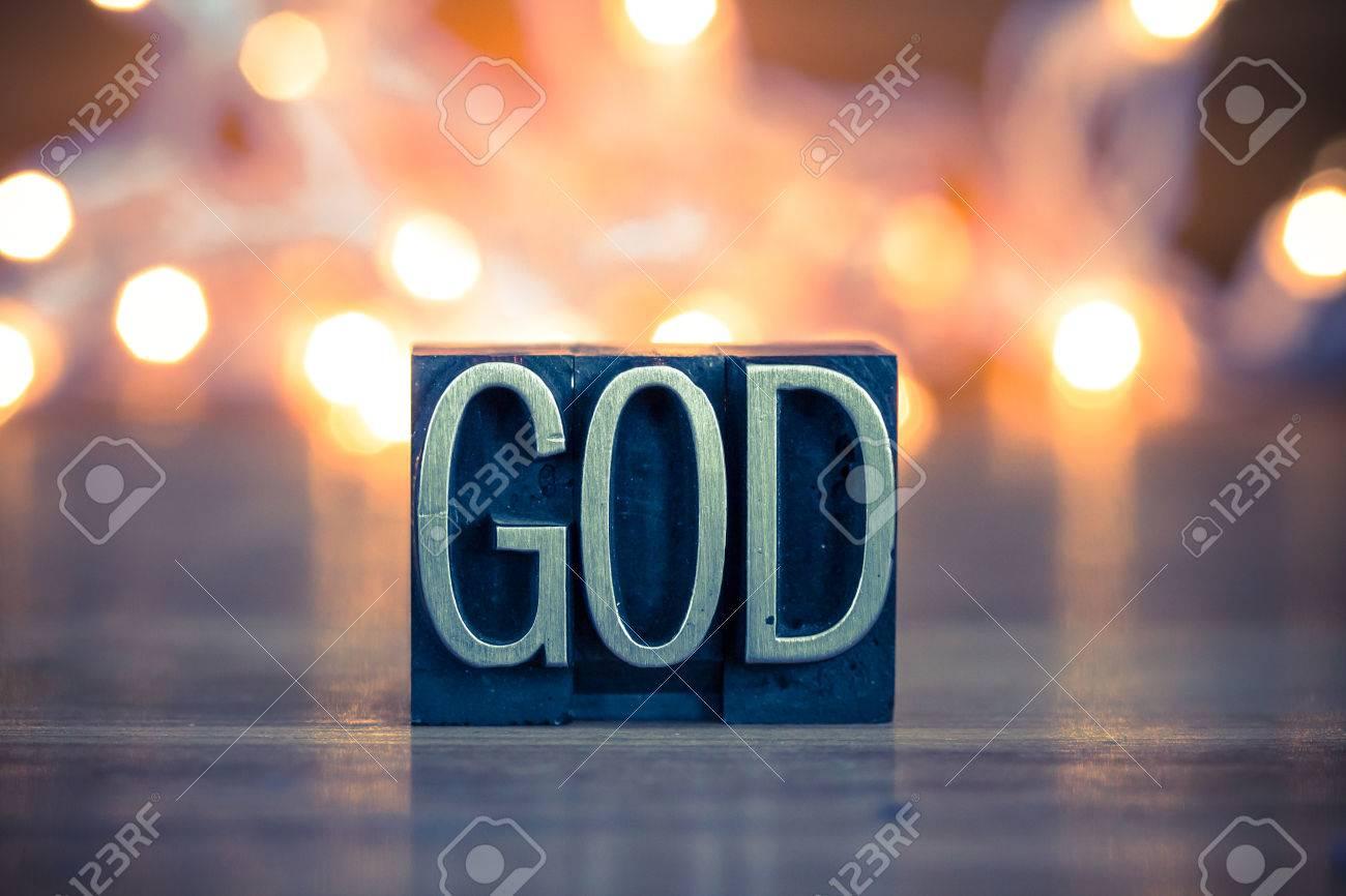 The word GOD written in vintage metal letterpress type on a soft backlit background. - 41854988