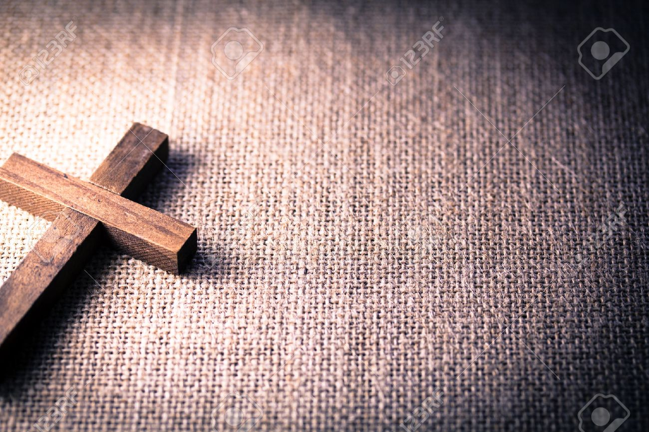 An aerial view of a holy wooden Christian cross on a burlap background. - 48011675