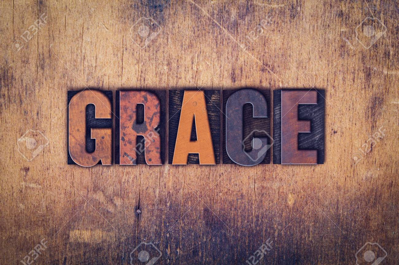 """The word """"Grace"""" written in dirty vintage letterpress type on a aged wooden background. - 50198476"""