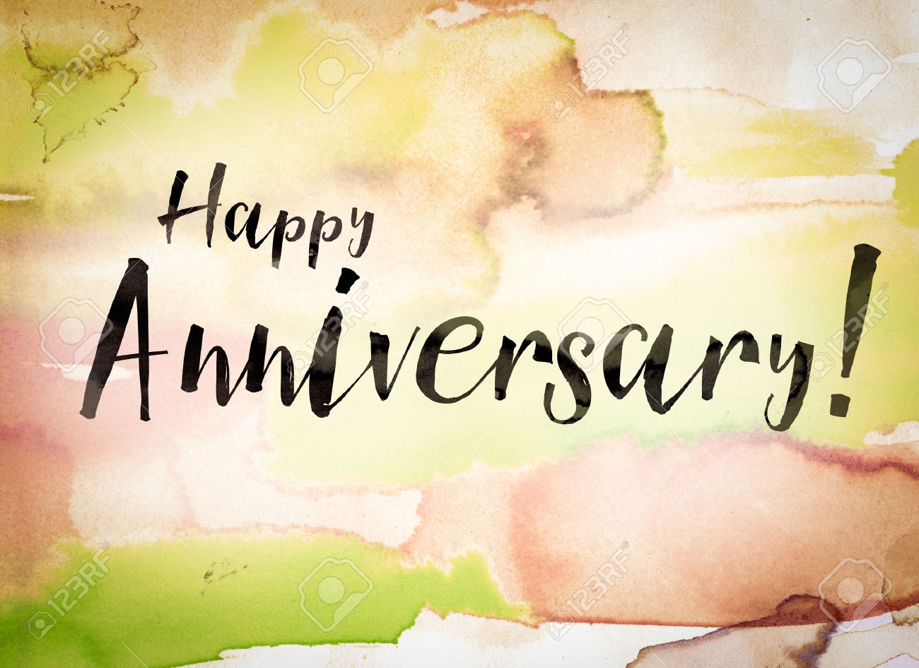 stock photo the word happy anniversary written in black paint on a colorful watercolor washed background
