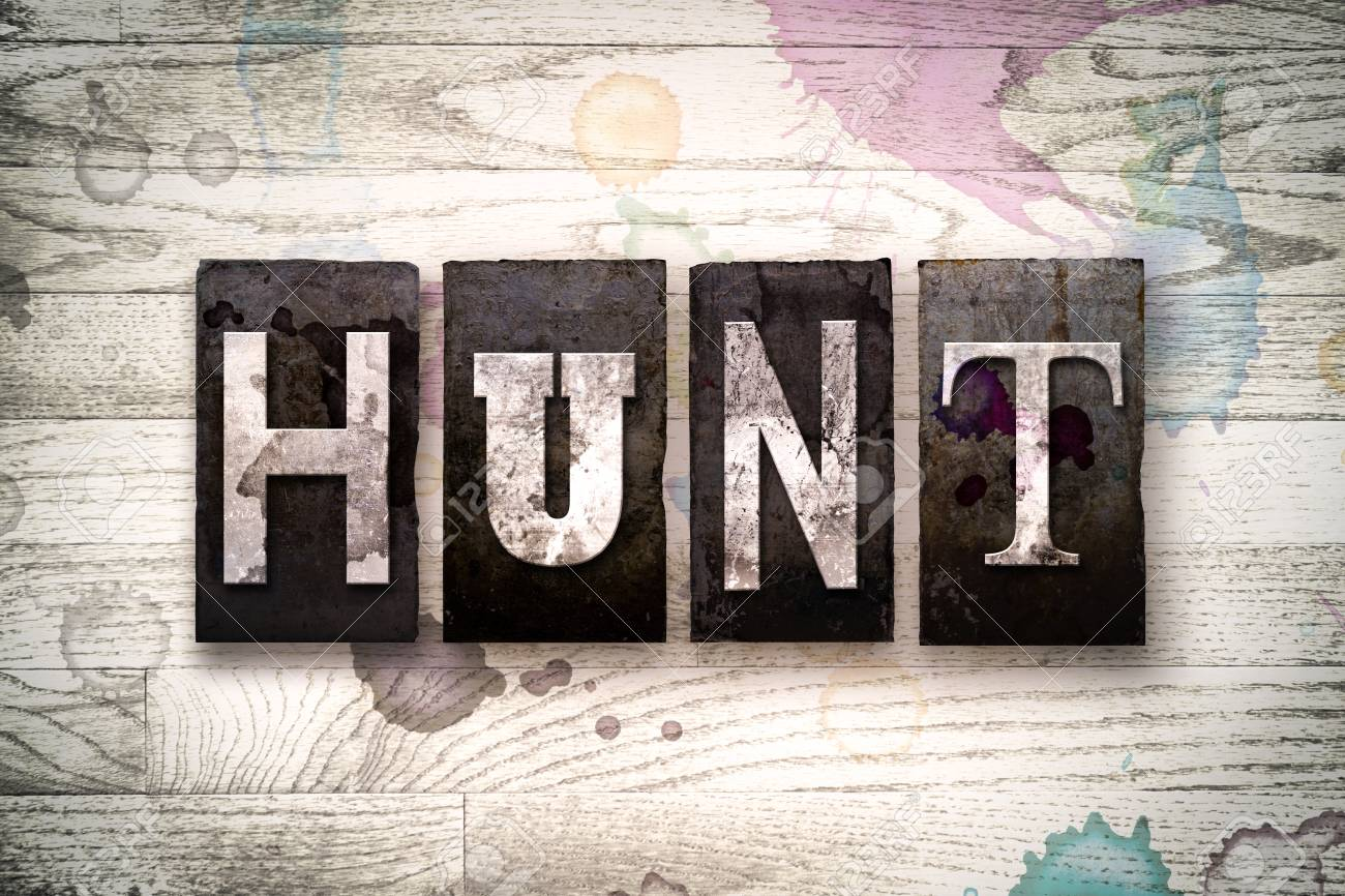 """The word """"HUNT"""" written in vintage dirty metal letterpress type on a whitewashed wooden background with ink and paint stains. - 61709437"""