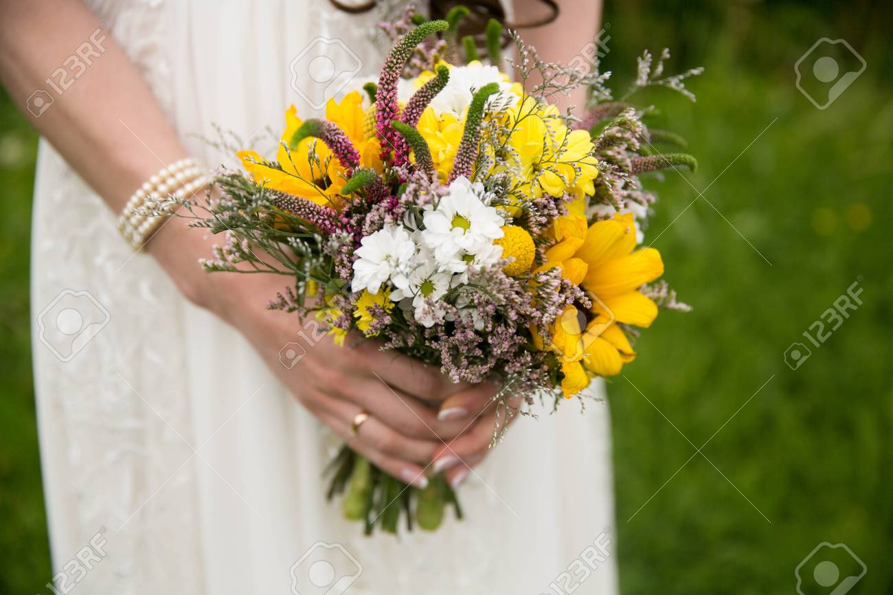 Bride In White Dress Holding A Bouquet Of Wild Yellow Flowers