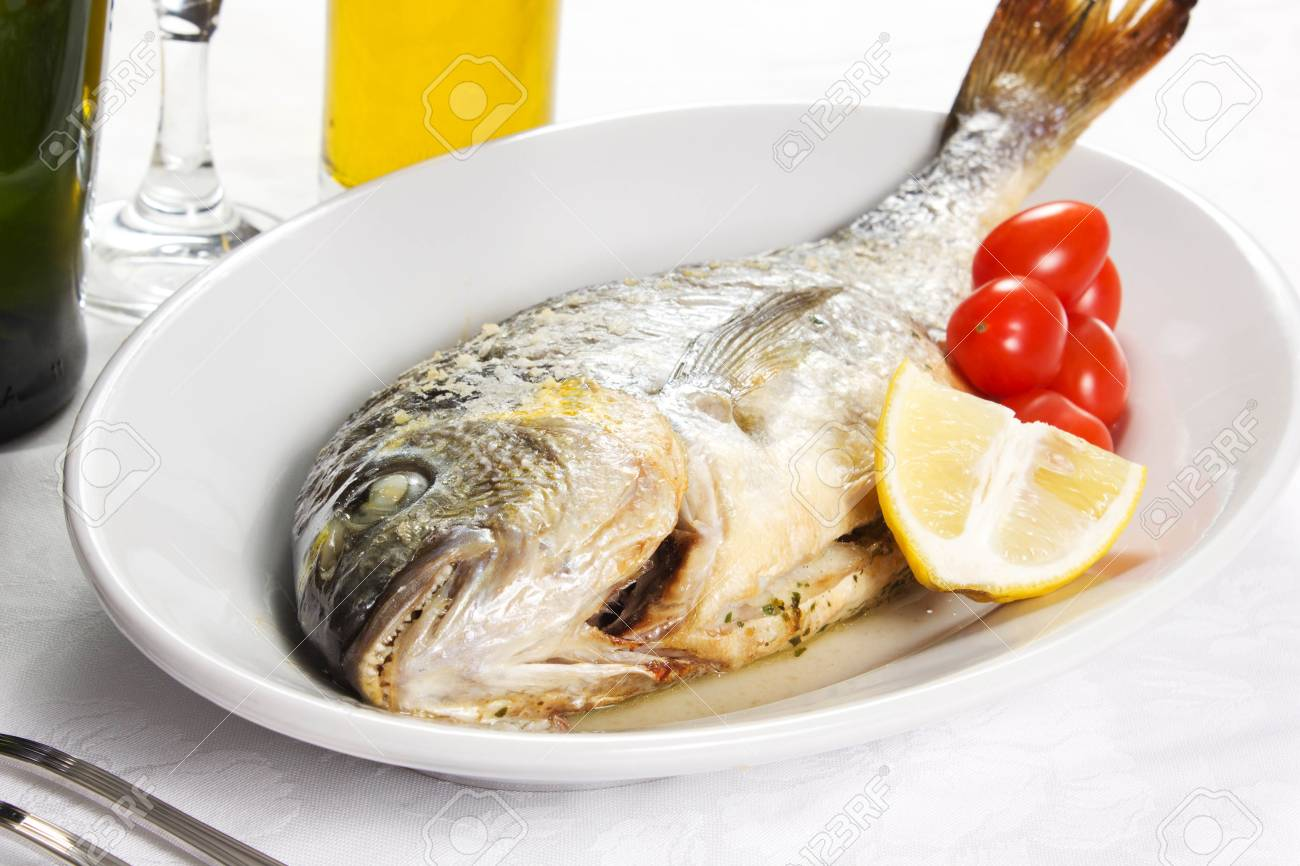 Mediterranean seafood concept  Sea bream on white plate with fresh herbs and colorful peppercorns on white background  Luxurious fish eating Stock Photo - 17720554