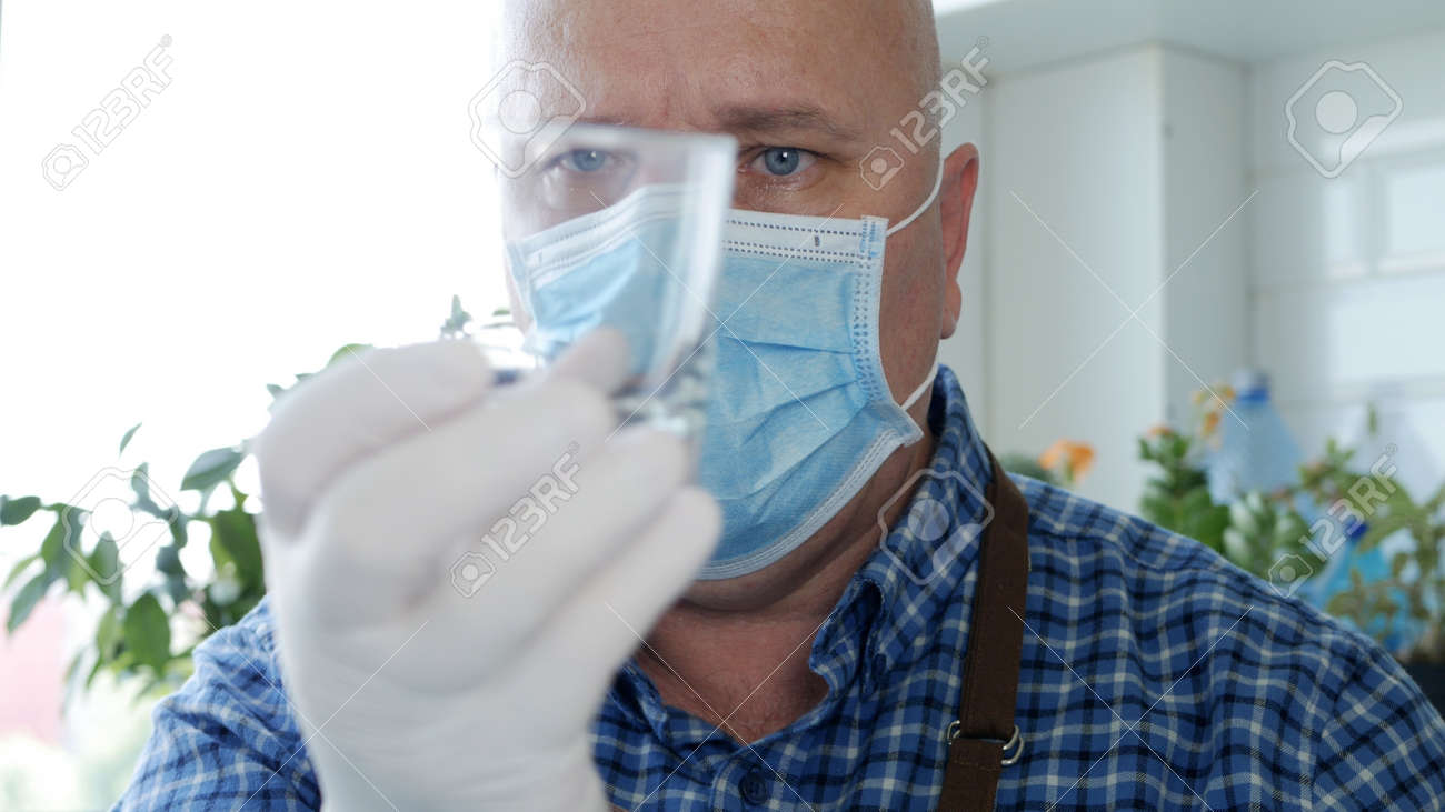 Image with a Bartender Wearing Protective Gloves and Face Mask Cleaning a Glass - 154968246