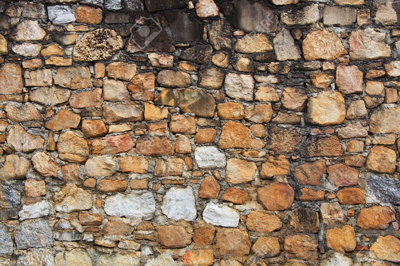 Una varietà di rocce fare un muro di pietra di sfondo o texture