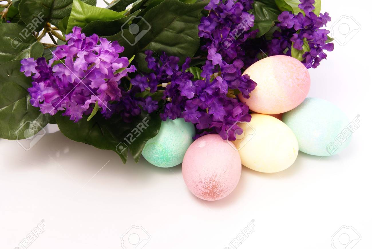 Colorful Pastel Easter Eggs Next To Purple Spring Silk Flowers