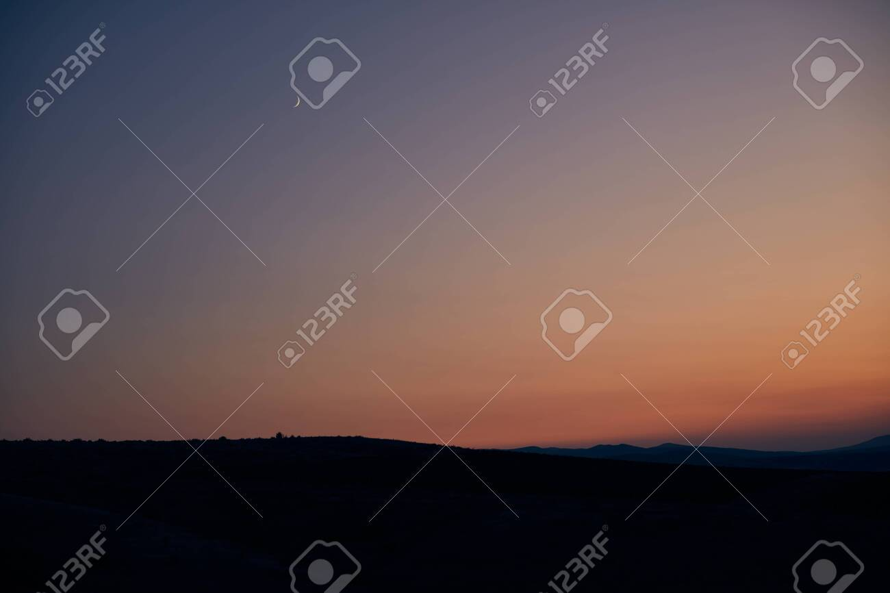 beautiful sunset and new moon on the background of hills - 144424979