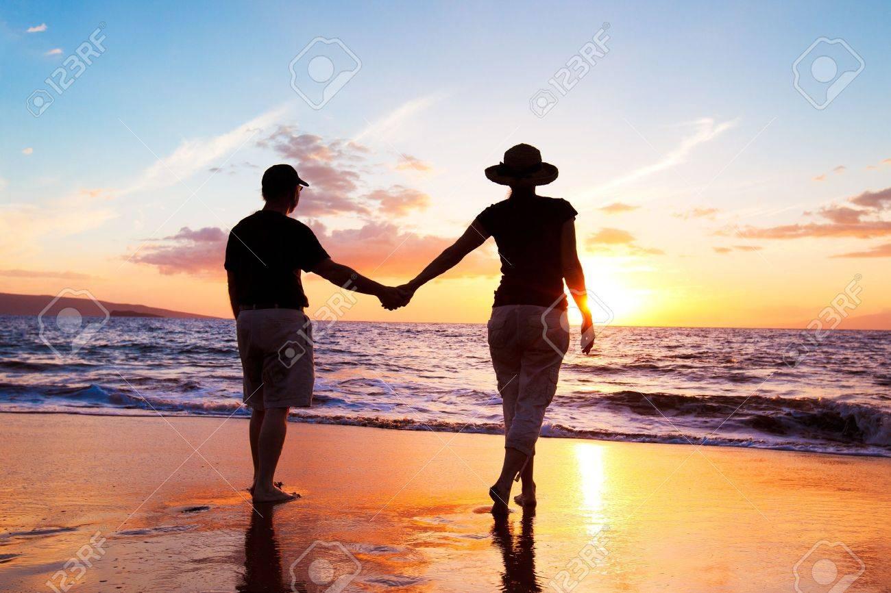 Senior Couple Enjoying Sunset at the Beach - 13184034