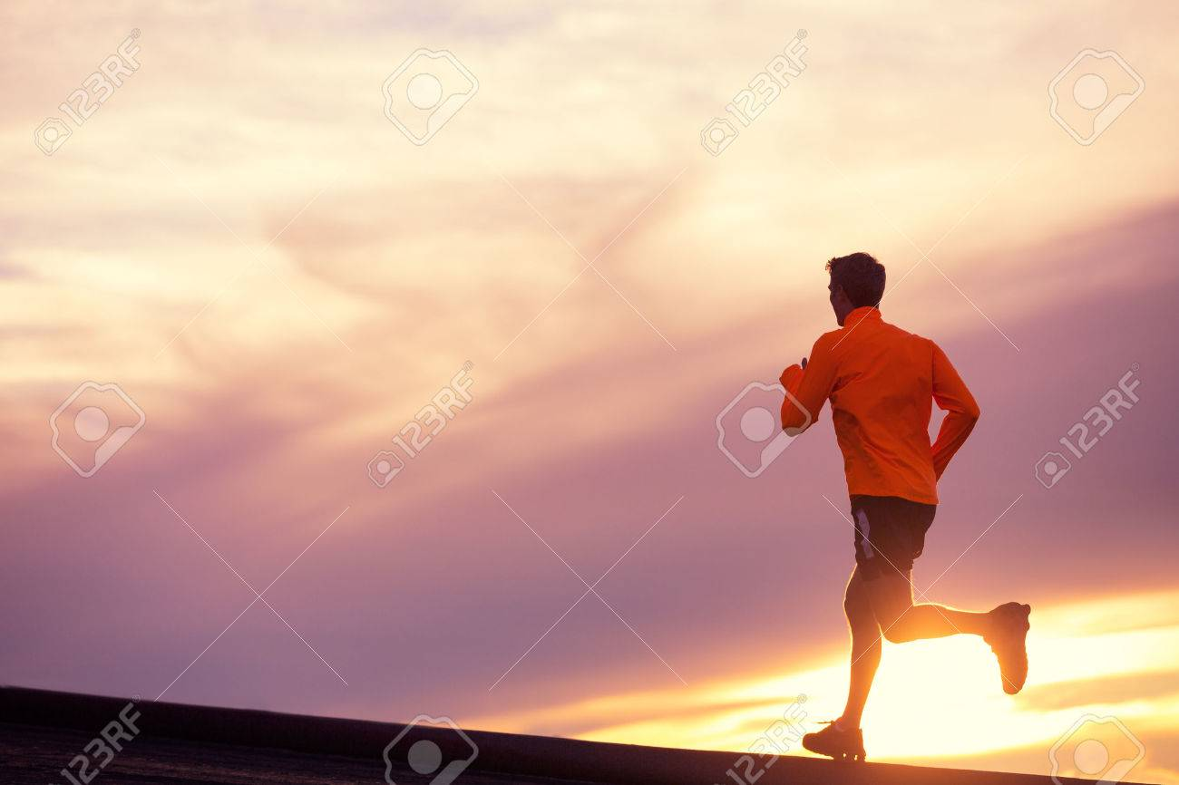 Male runner silhouette, Man running into sunset, colorful sunset sky - 23406591