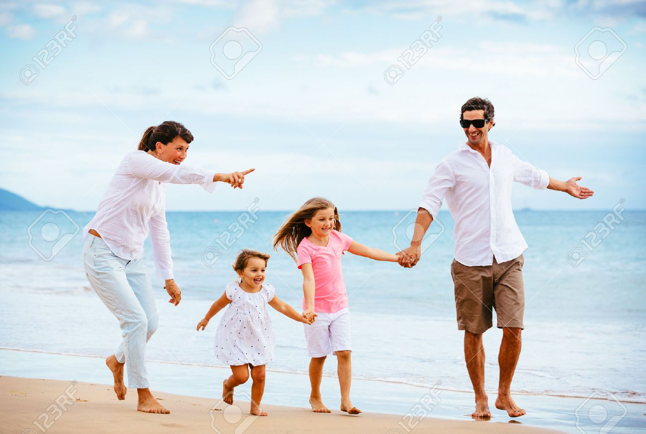 03bdf981b32 Happy young family walking on the beach at sunset. Happy Family Lifestyle  Stock Photo -