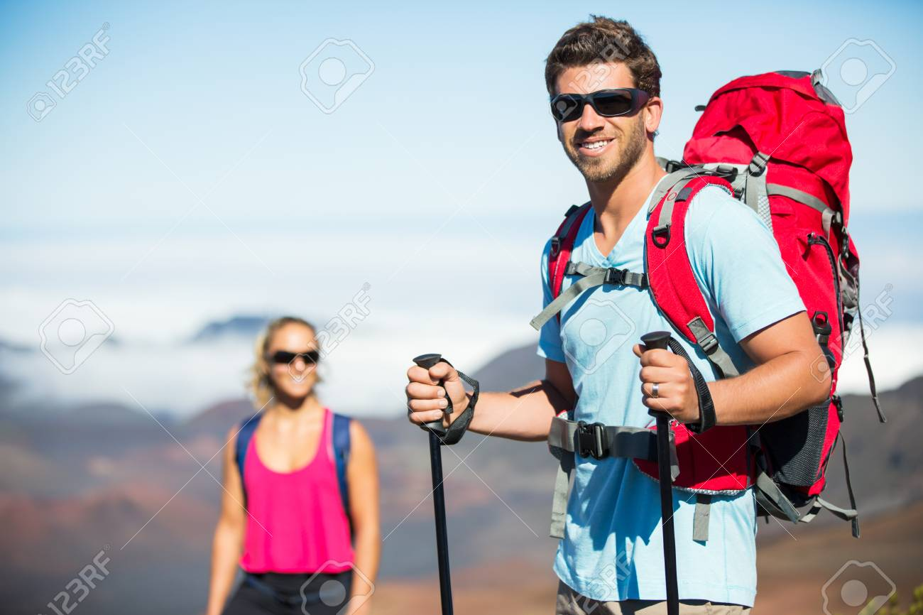 7282a2b78e6197 Healthy lifestyle outdoor adventure concept. Man and woman hiking on beautiful  mountain trail. Trekking and backpacking in the mountains.