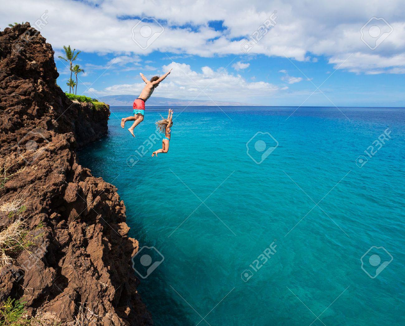 Summer fun, Friends cliff jumping into the ocean. - 30193394