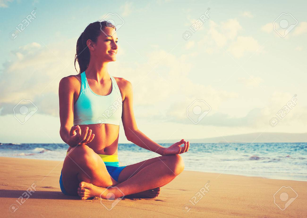 Happy young woman practicing yoga on the beach at sunset. Healthy active lifestyle concept. Stock Photo - 43698738