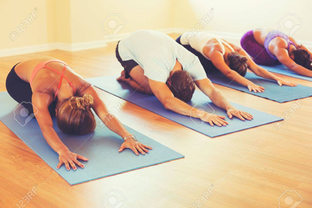 Yoga Class Group Of People Relaxing And Doing Childs Pose Wellness