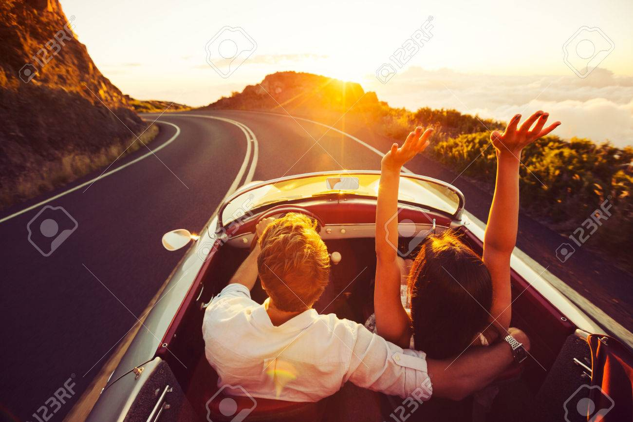 Happy Couple Driving on Country Road into the Sunset in Classic Vintage Sports Car Stock Photo - 44181473