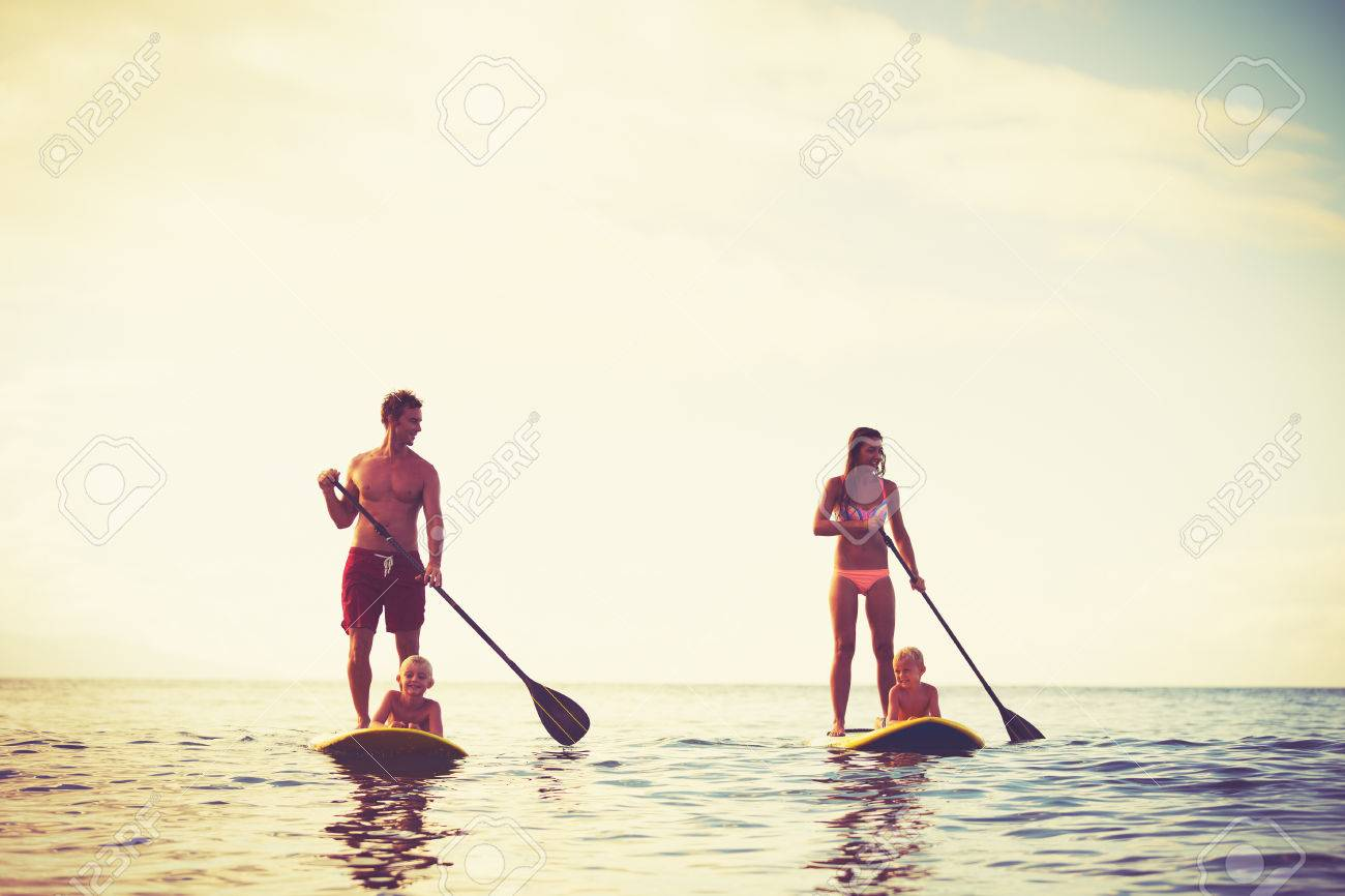 Family Having Fun Stand Up Paddling Together in the Ocean at Sunrise Stock Photo - 46094492