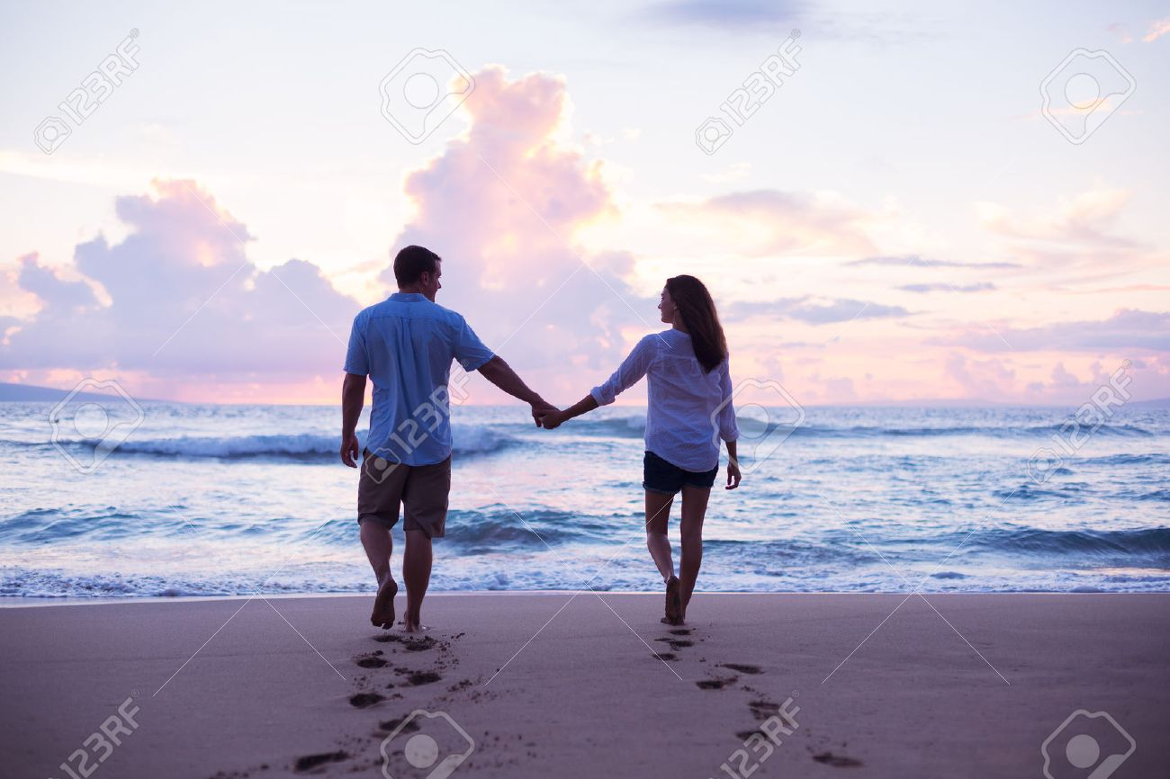 Young Lovers Walking On The Beach At Sunset Tropical Vacation