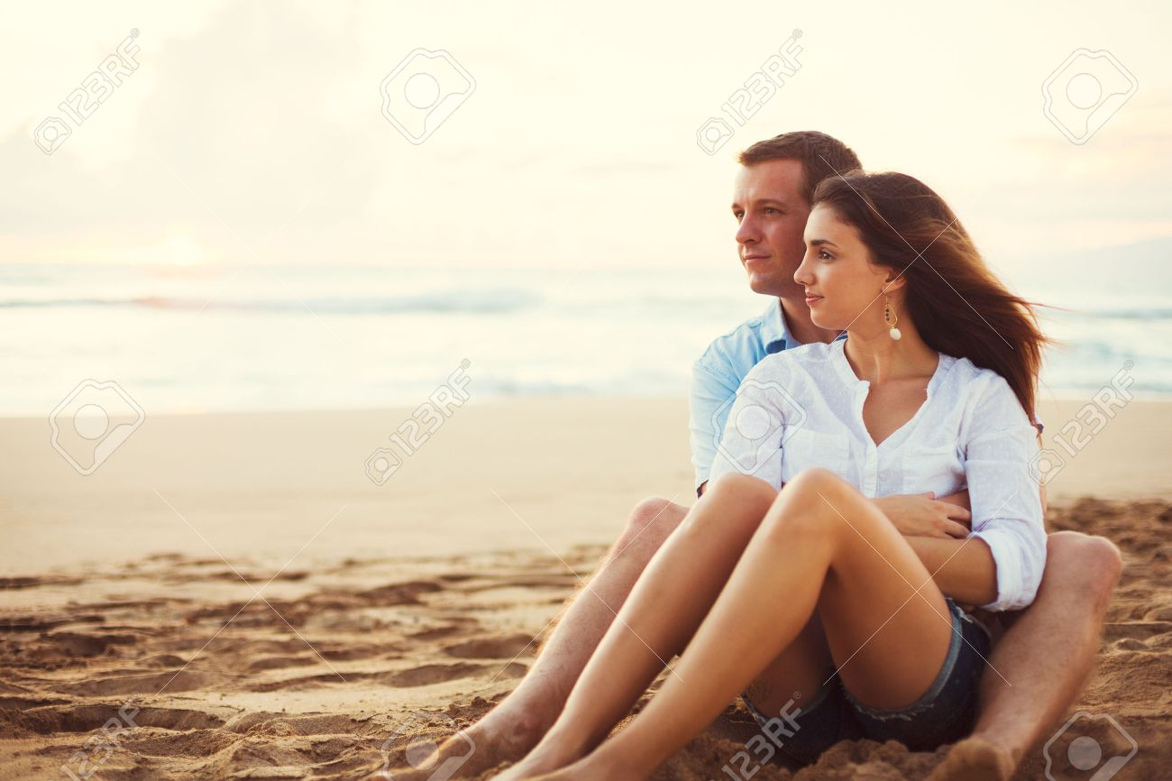 Happy Young Romantic Couple Relaxing on the Beach Watching the Sunset. Vacation Honeymoon Getaway. Stock Photo - 46085551