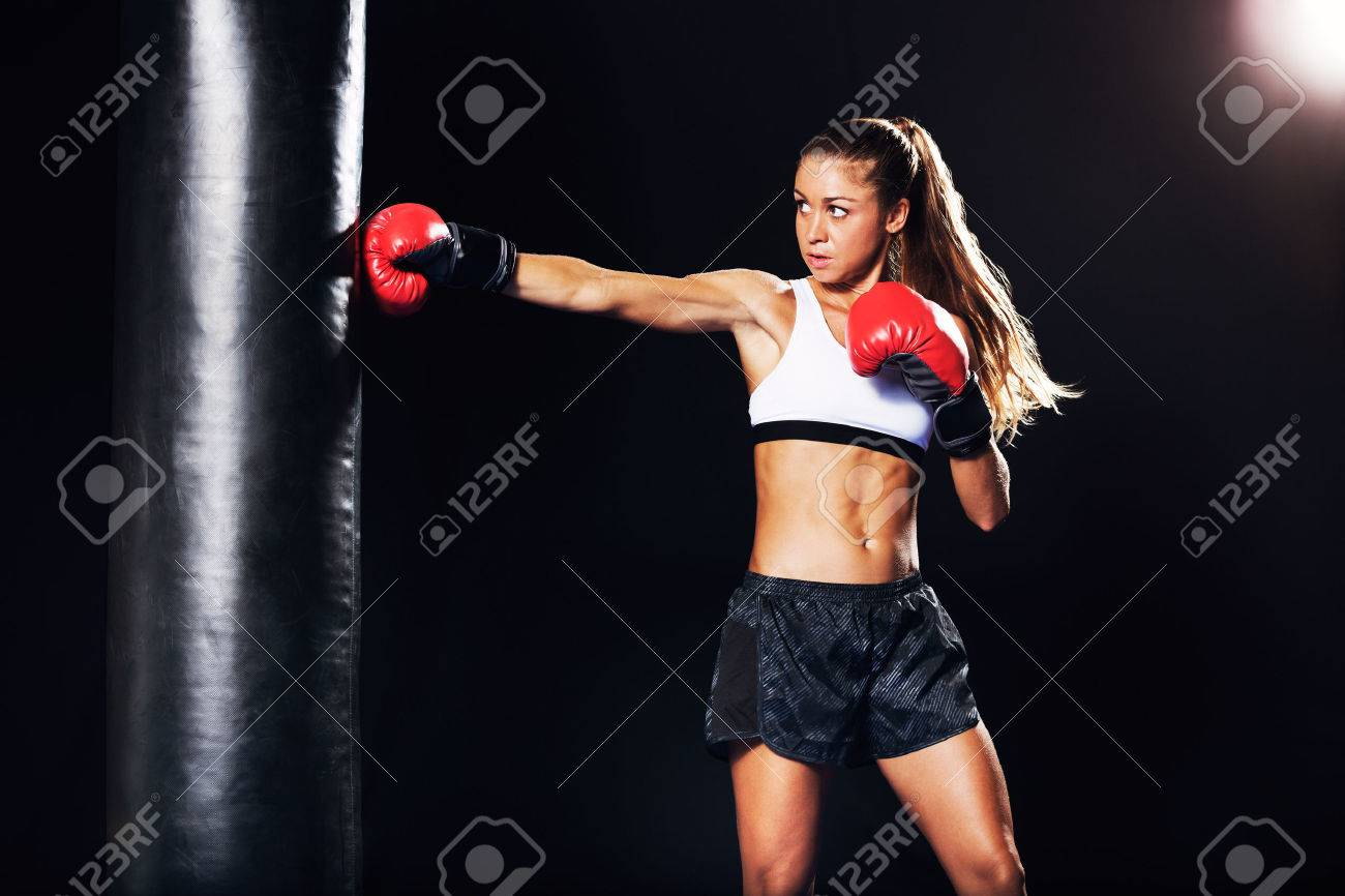 9411b1bb6b15 Beautiful Fitness Woman with the Red Boxing Gloves. Attractive Female Boxer  Training Punching a Heavy