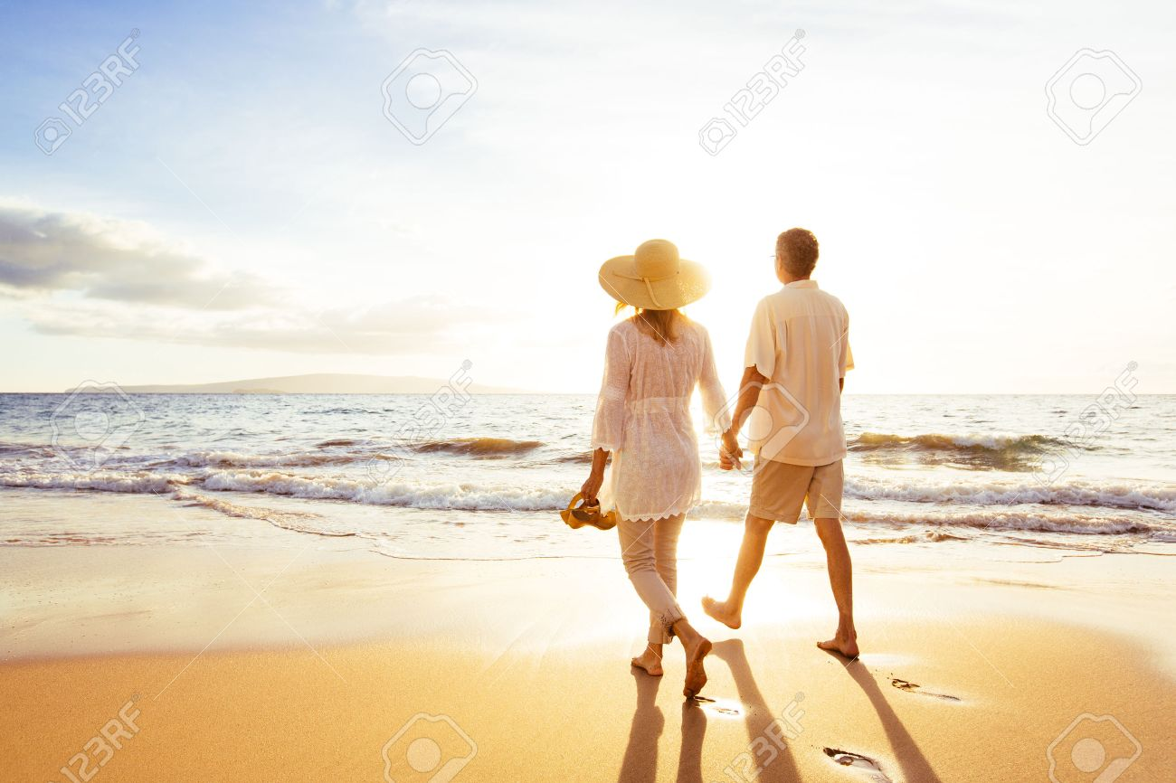 Happy Romantic Middle Aged Couple Enjoying Beautiful Sunset Walk on the Beach. Travel Vacation Retirement Lifestyle Concept Stock Photo - 49495428