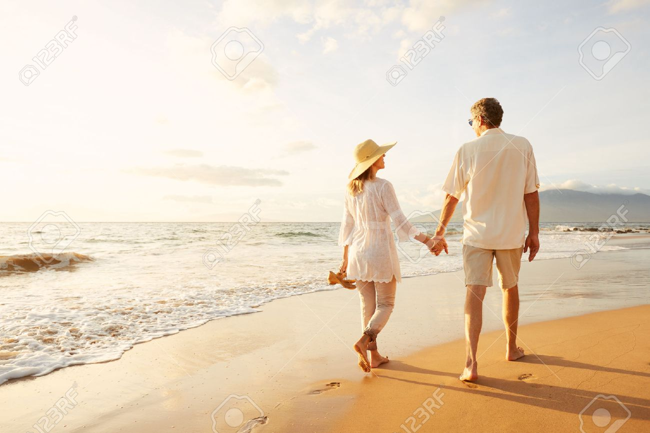 Happy Romantic Middle Aged Couple Enjoying Beautiful Sunset Walk on the Beach. Travel Vacation Retirement Lifestyle Concept Stock Photo - 49643671