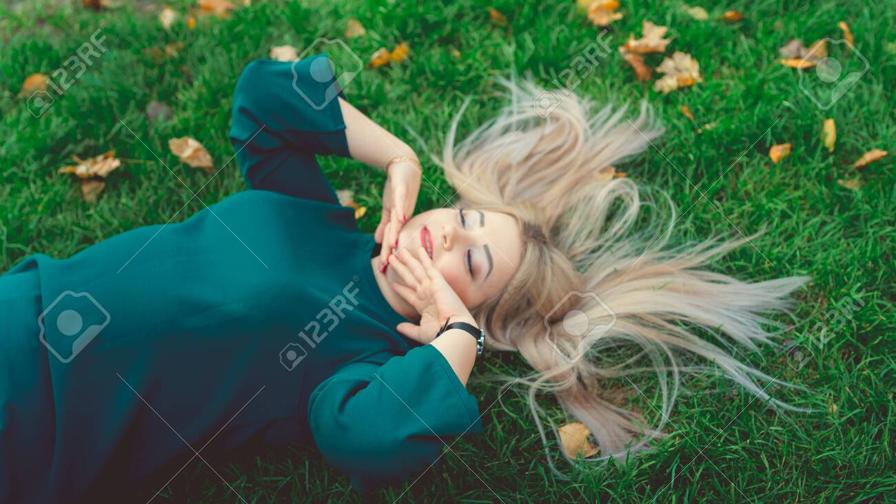 A portrait of a beautiful girl, lying on the grass. A charming woman lies on the green grass with yellow leaves - 133191136