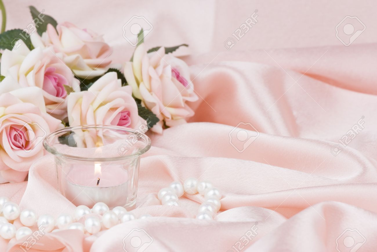 Pink Roses Burning Candle And A Pearl Necklace On A Silk Fabric